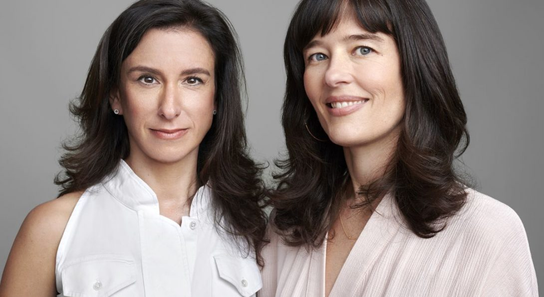 Two dark-haired early-middle-aged women in light-colored tops